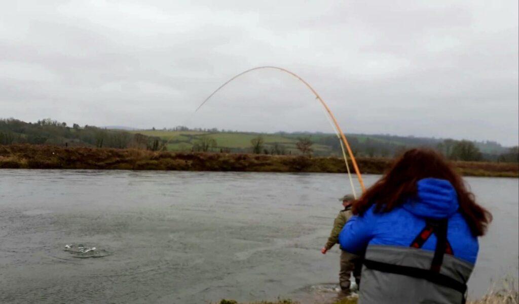 Glenda giostra un pesce mentre Patrick Devennie è pronto ad aiutarla a Careysville